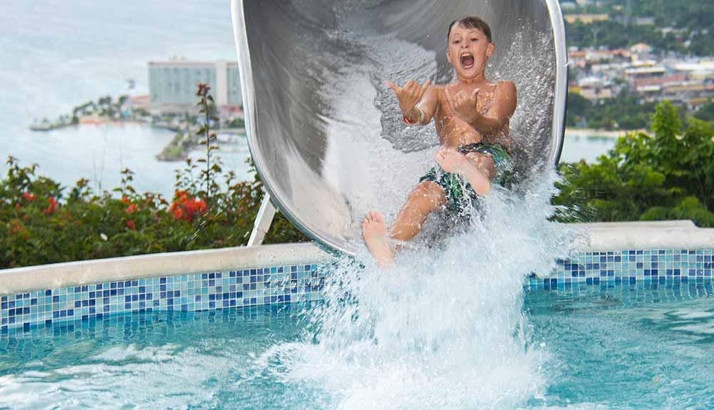 Young boy excited to reach the end of a water slide, about to drop into the pool