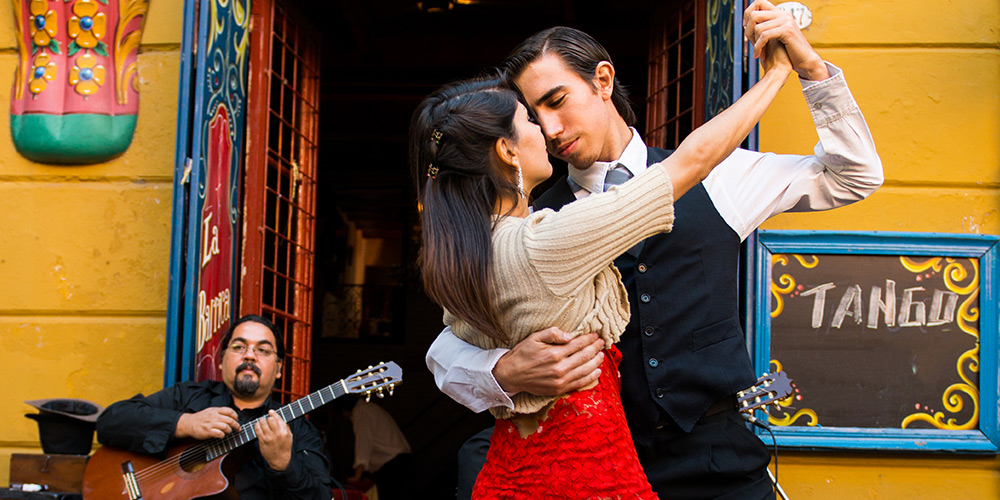A couple dances the tango in front of a live gutar player sitting in front of a bright yellow building, a sign to the right of the door reads Tango
