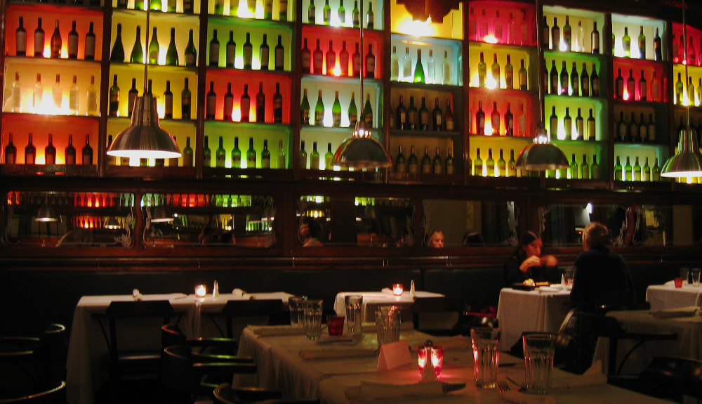 A fine dining restaurant with wine bottles stacked against a colourful backlit background, candles adding a romantic ambiance to the tables