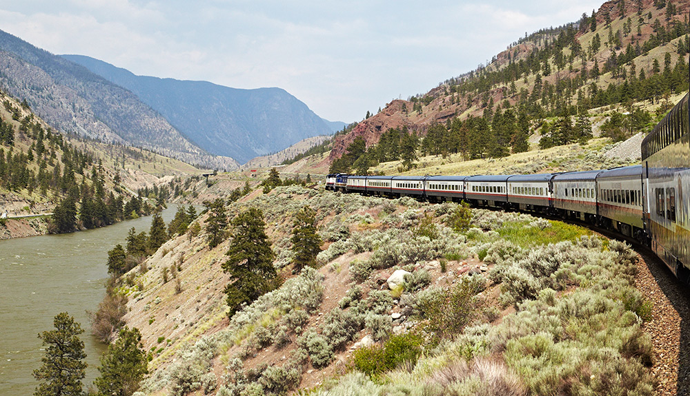 A train going through the rocky mountains.