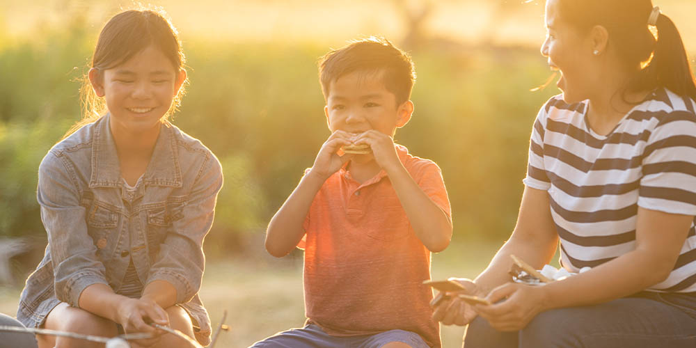 A woman and two kids eat s'mores at sunset