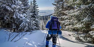 Person wearing winter coat and snow pants with a loaded backpack as they hold poles making their way up a snowy hill