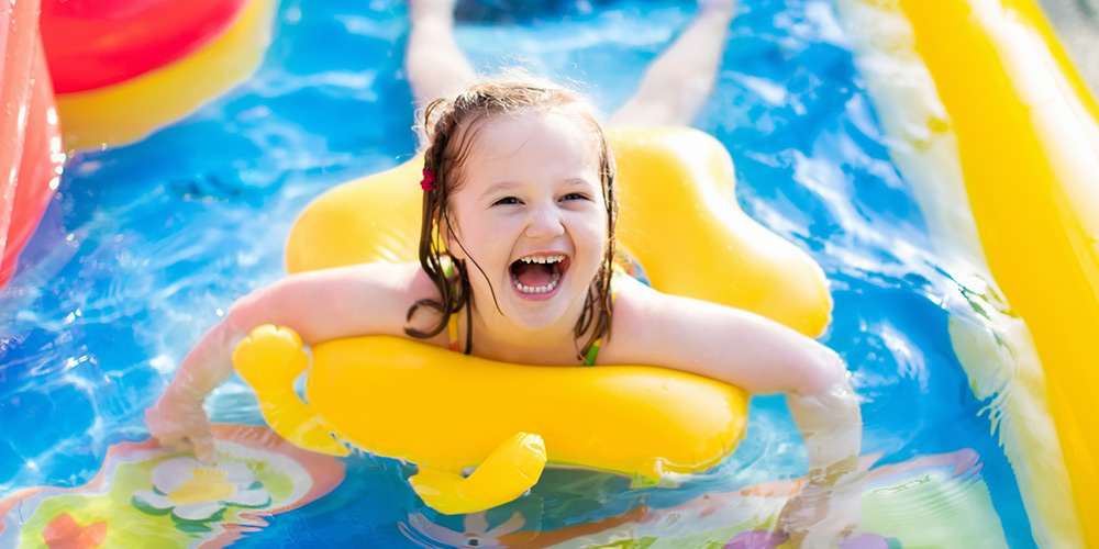A young girl giggles with delight while playing in a pool, swimming with a bright yellow pool ring