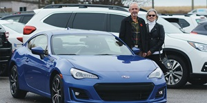 CAA Give and Get contest winners Randy and Linda Ward standing with a blue Subaru BRZ sports car at Whitby Subaru in Ontario