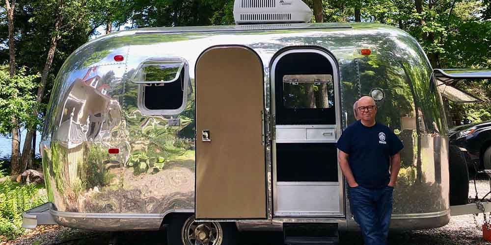 Terry O'Reilly host of CBC Radio One stands outside of his metal vintage trailer