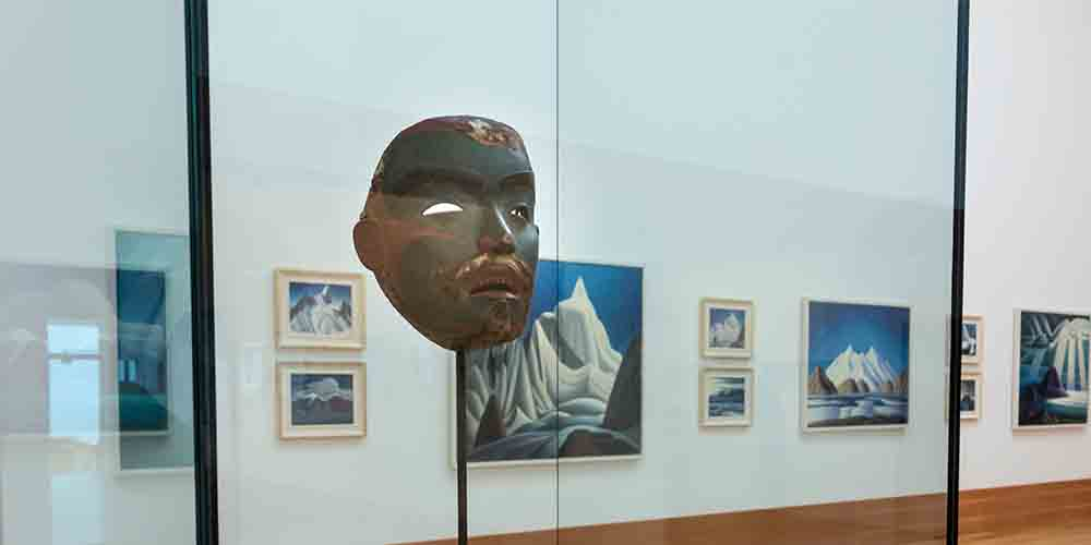 A mask is shown in a gallery with paintings in the background