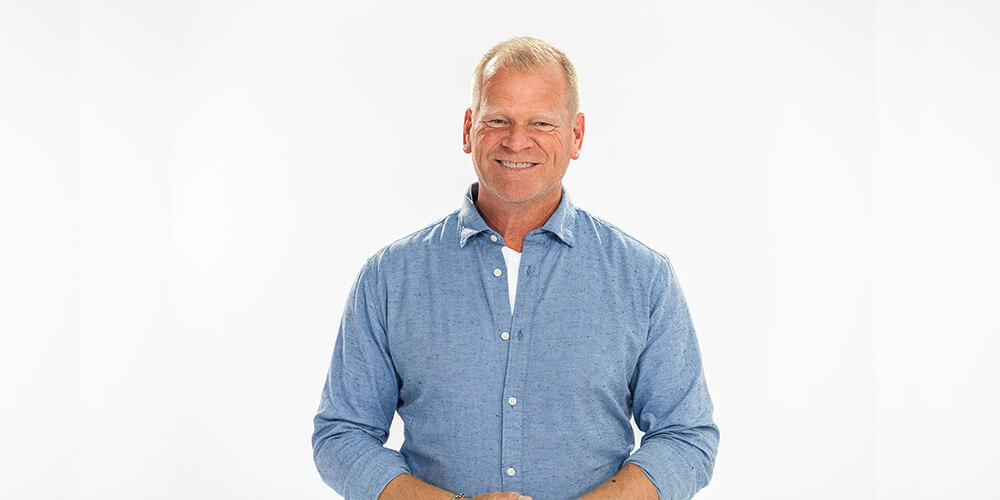 TV personality and contractor, Mike Holmes, dressed in a blue button down shirt
