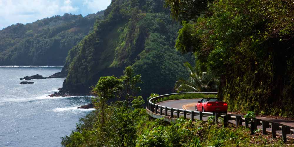 Red convertible drives on the Hana Highway along the coast of Maui