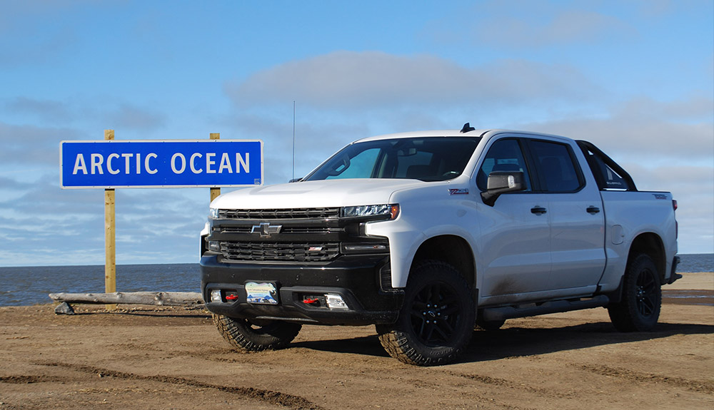 White Ford truck parked in front of sign that reads Arctic Ocean near waterfront