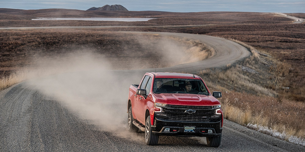 Red Ford truck speeds down an dusty, empty winding road on the Inuvik-Tuktoyatuk highway
