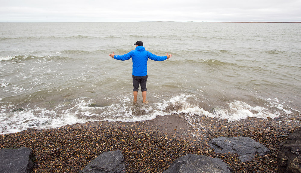 A young man in blue coat and black cap is seen wading in the gentle waves of the ocean on a rocky shoreline
