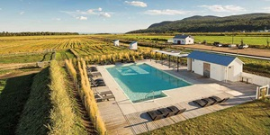 The outdoor pool at Le Germain Charlevoix Hotel and Spa in Quebec surrounded by farmland