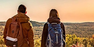 Two hikers are shown pausing to take in the view of the Kawarthas Northumberland region in the fall
