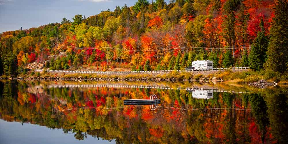 A truck pulls an RV on a road with vivid fall foliage alongside it