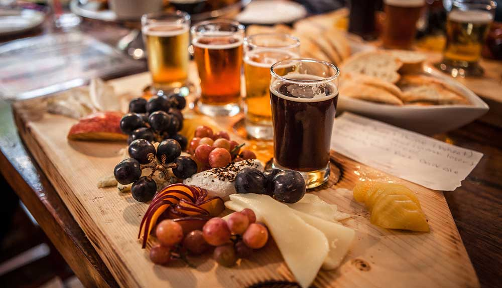 A flight of beers are shown on a board with cheese and grapes