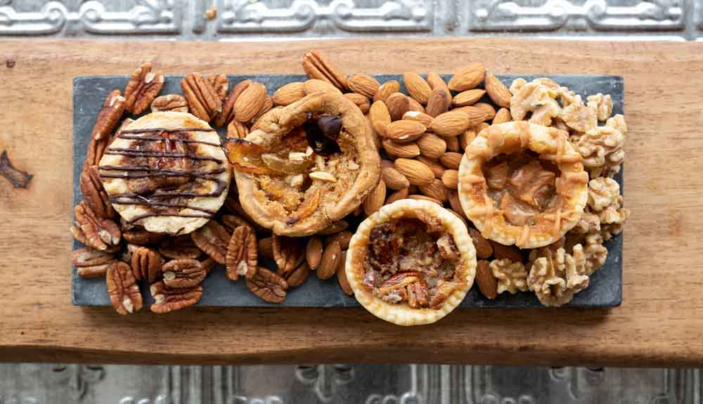 An overhead photo shows four butter tarts on a wood board with almonds, pecans and walnuts