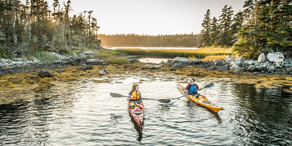 Blonde woman and brunette man with lifejackets on kayaking on fresh water at sunset