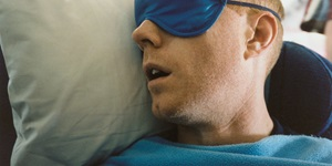 A man cozied up in a blue fleece blanket sleeps against a grey pillow, a soft blue eye mask cover his eyes