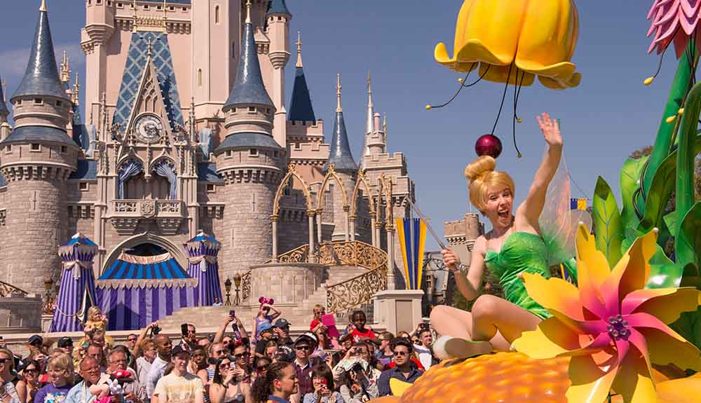Woman dressed as Tinkerbell waving from a float in a parade as it passes by the entrance to the Magical Kingdom castle