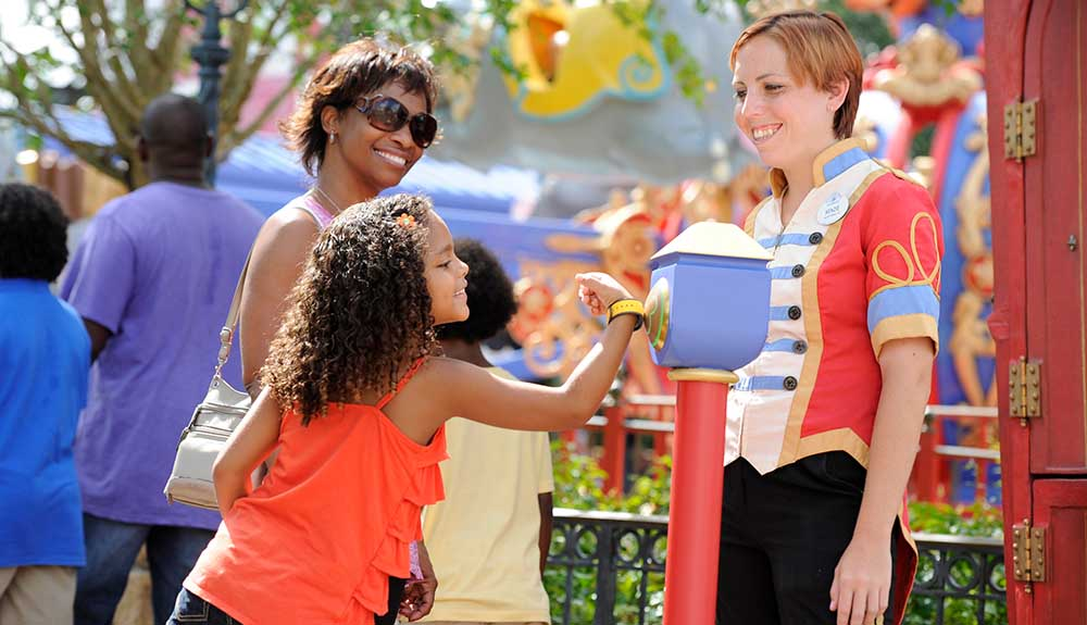 Little girl uses her FastPass+ pass with her mom at a Disney resort