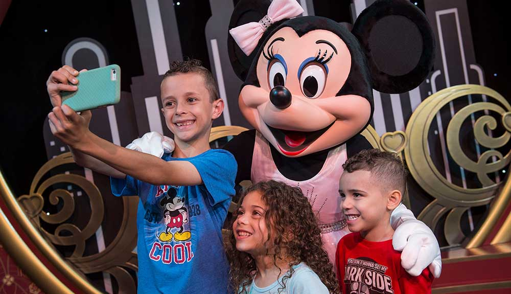 Little boy taking a selfie with Minnie Mouse and two other kids