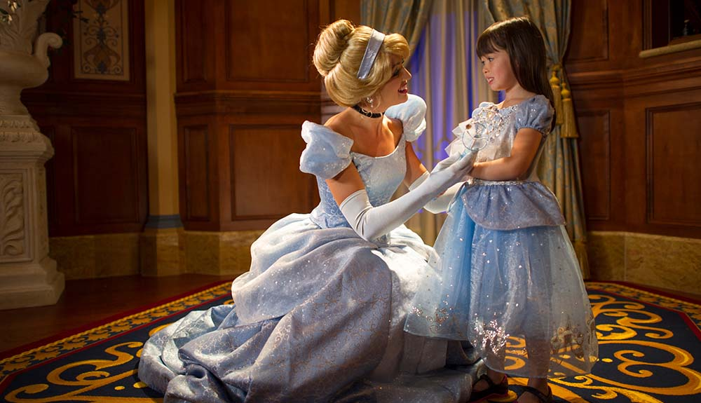 Woman dressed as Cinderella elegantly squatted down as she talks to a little girl wearing a princess dress