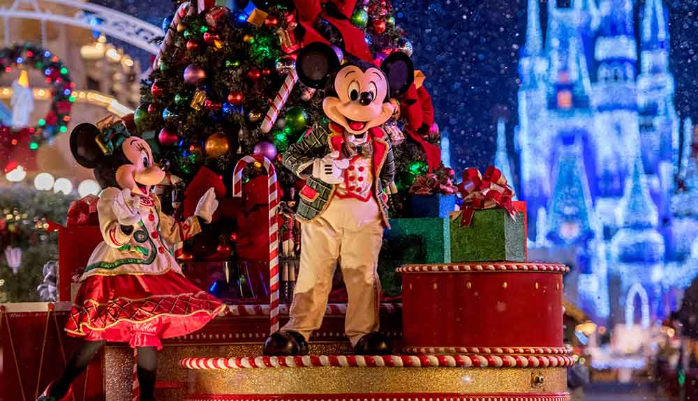 Micky and Minnie Mouse dressed for the holidays in front of a Christmas tree while on a float during a parade