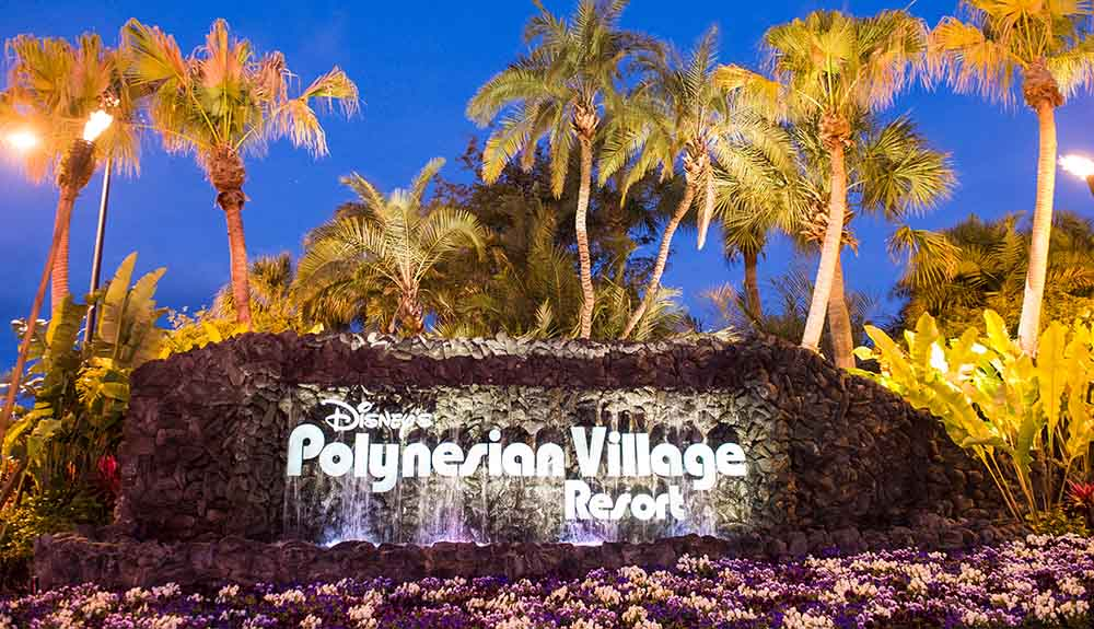 Polynesian Village resort sign at night surrounded by palm trees