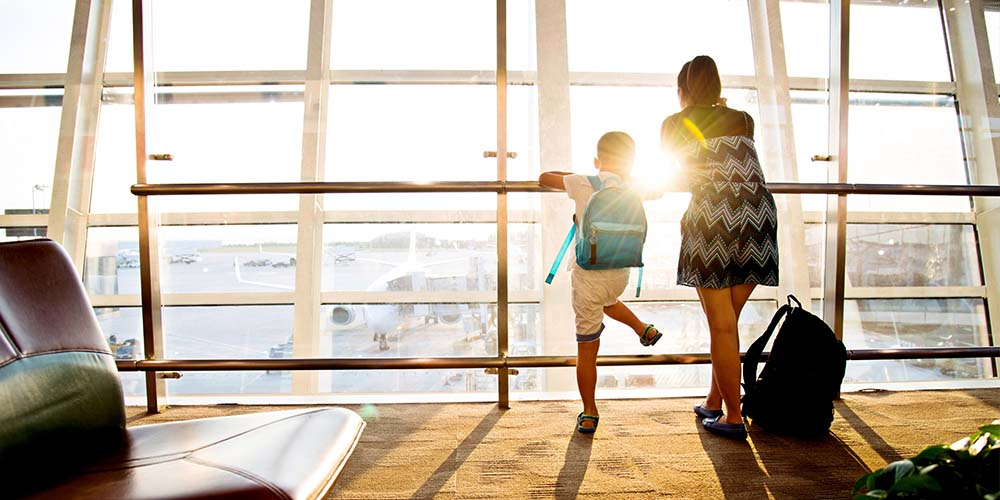 The back of a woman with backpack on the floor and child with backpack from inside the airport looking out as the airplanes