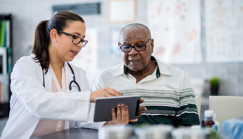 Doctor reviewing chart with older man