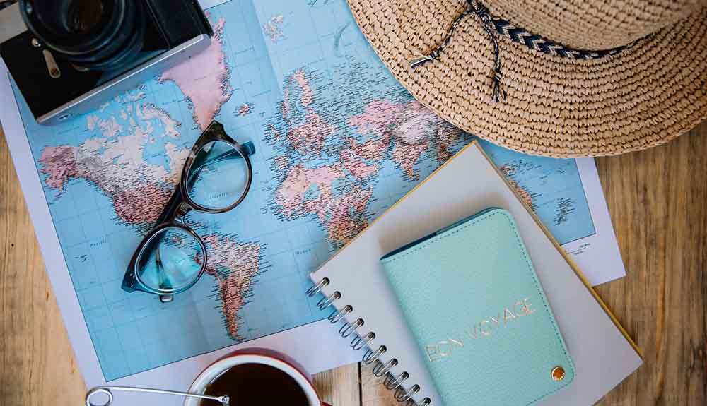 World map on table covered by camera, glasses, sun hat and notebooks