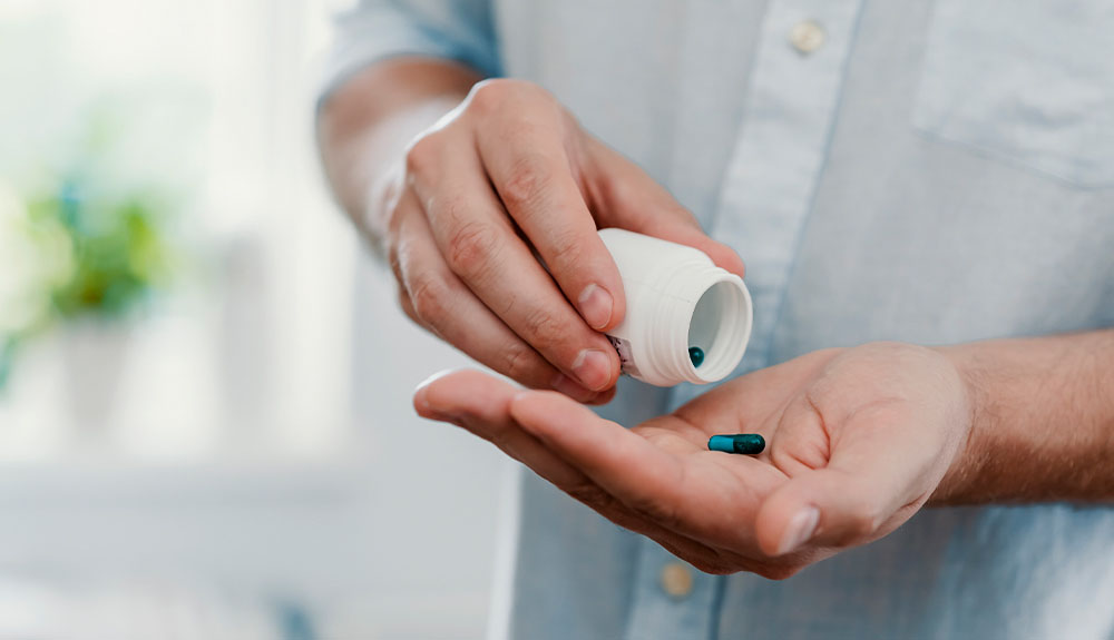 Person shaking pills from a container into their palm