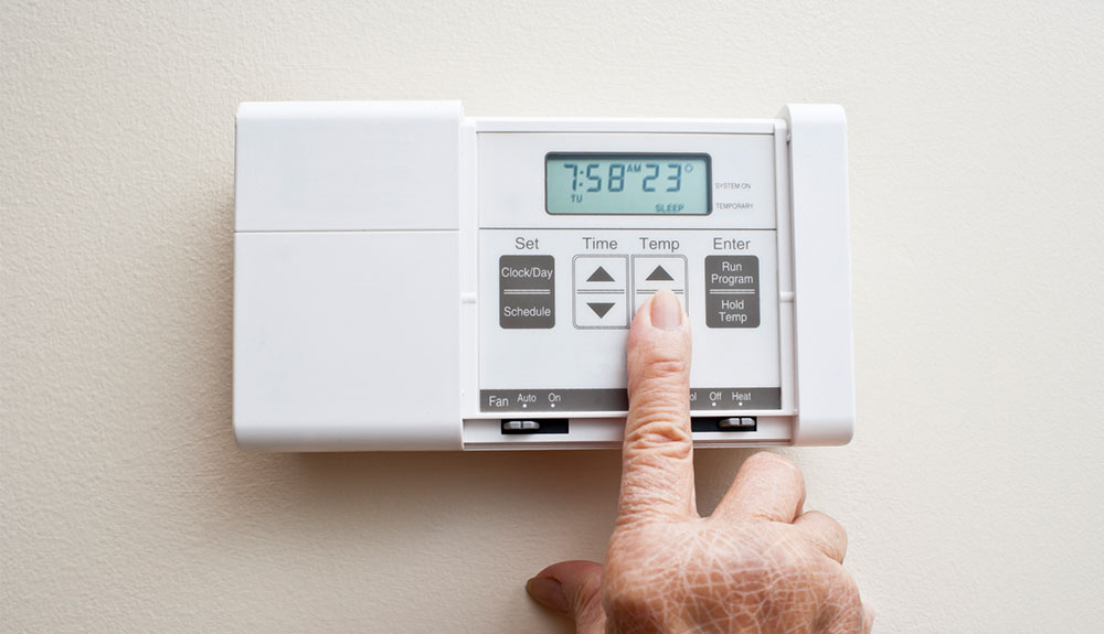 Person lowering the heat on a digital thermostat