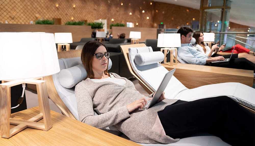 Woman sitting on lounger at airport typing on laptop