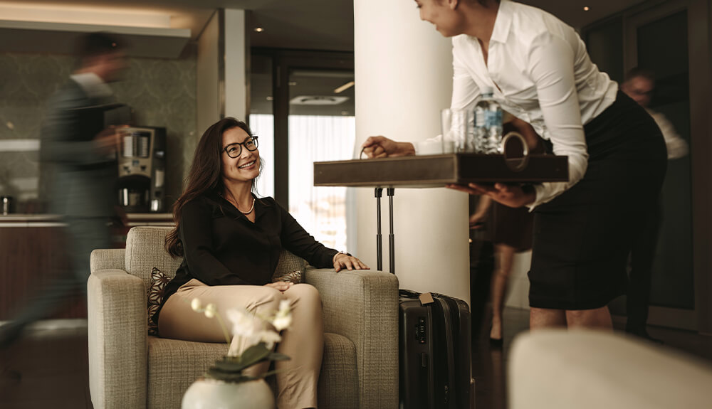 Woman with tray serving drinks to passenger in airport lounge