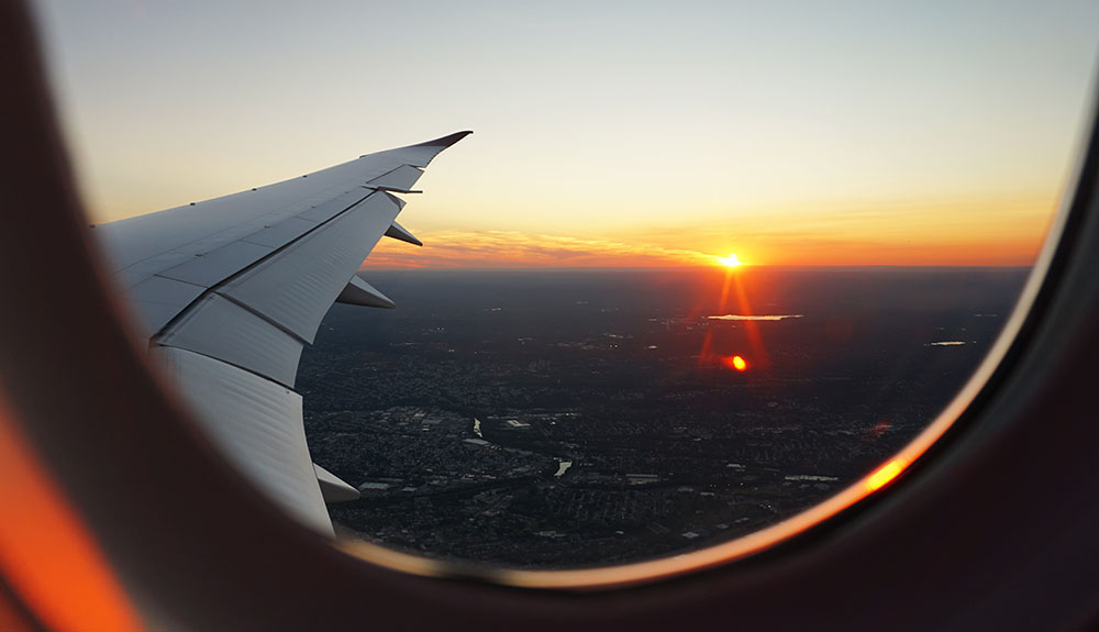 Passenger window of an airplay overlooking the wing while the sun sets