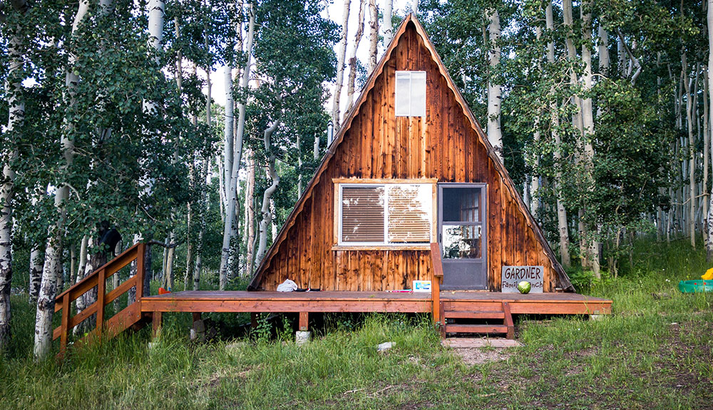 Unique alternative accommodation in the form of a triangle shaped cabin made of wood with a wraparound porch