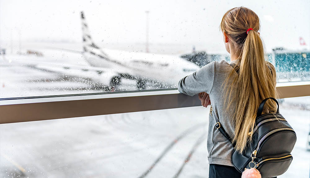 Woman with backpack standing at airport window watching the rain
