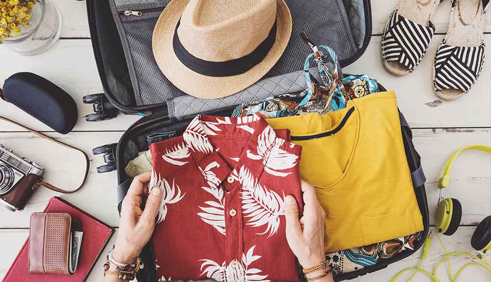 Hands placing folded tropical shirt into suitcase along with straw hat and sandals