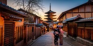 Two women dressed in kimonos walking on street in Kyoto, Japan, lined with traditional buildings at dusk