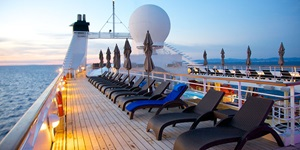 Top deck of a cruise ship featuring many loungers and lights at sunset