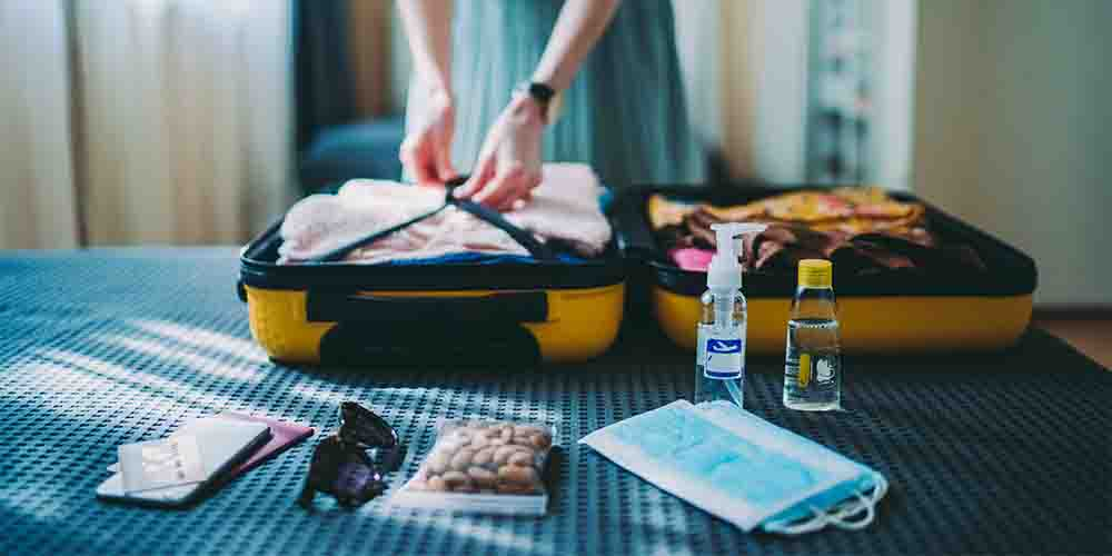A woman packs a small suitcase