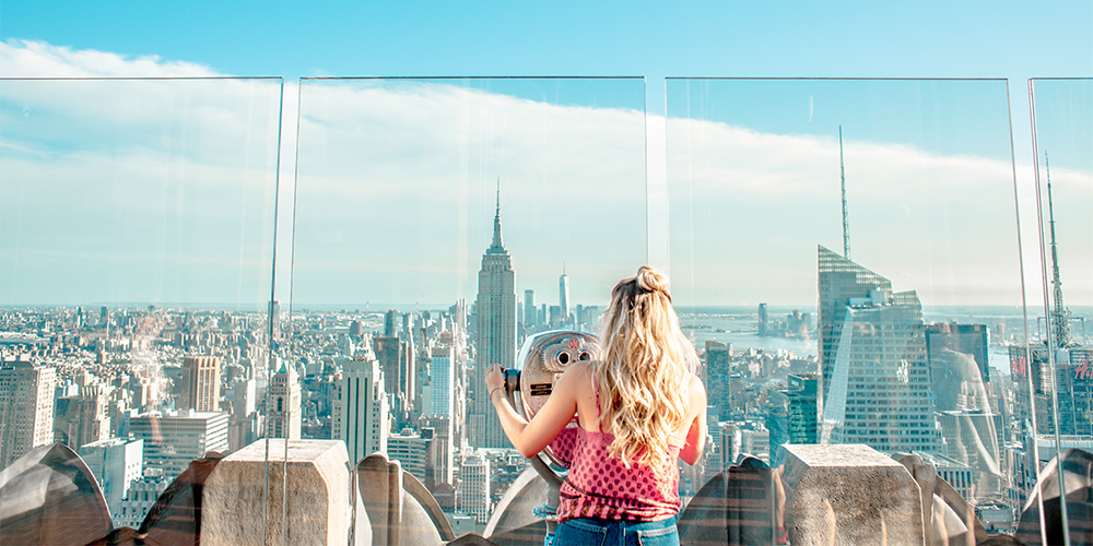A traveller looks out from the observation deck of the Empire State Building, in New York, New York