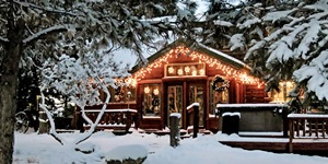The exterior of a holiday cabin decorated with lights and wreaths with snow on the ground