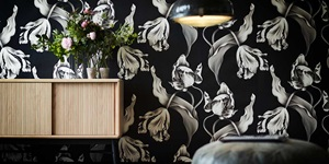Dark floral wallpaper behind a light wood shelving unit with fresh flowers on top