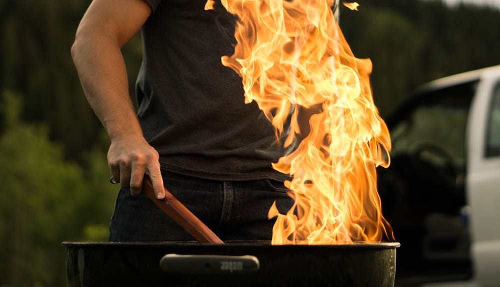 A person stokes a grill, the flame shooting up