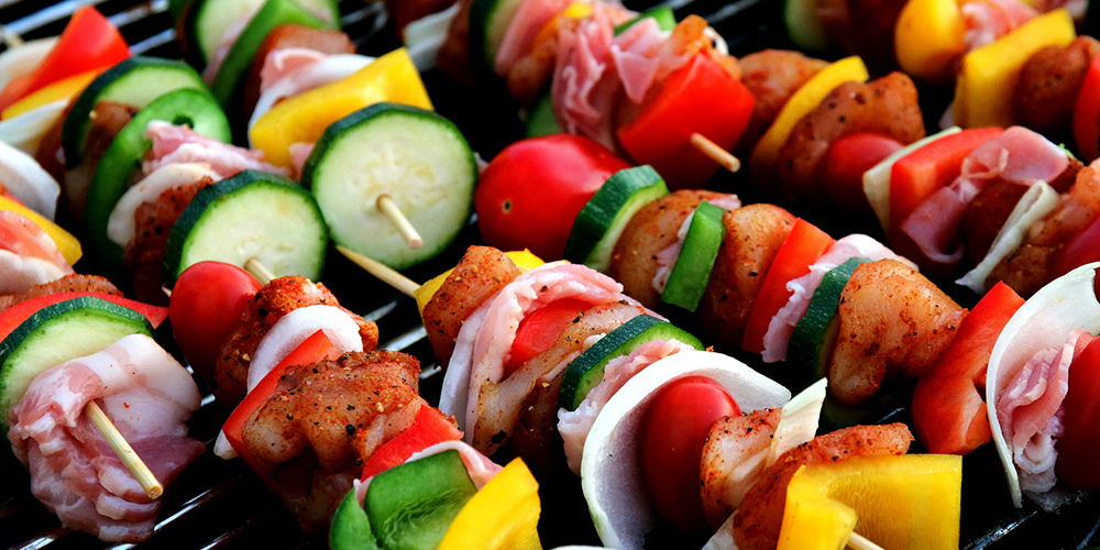 Vegetable and meat kebabs skewered with colourful bell peppers, chicken, red onion, cherry tomatoes and zucchini on a grill