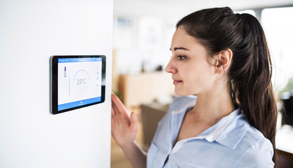 A woman stands in front of a smart thermostat mounted on a wall.