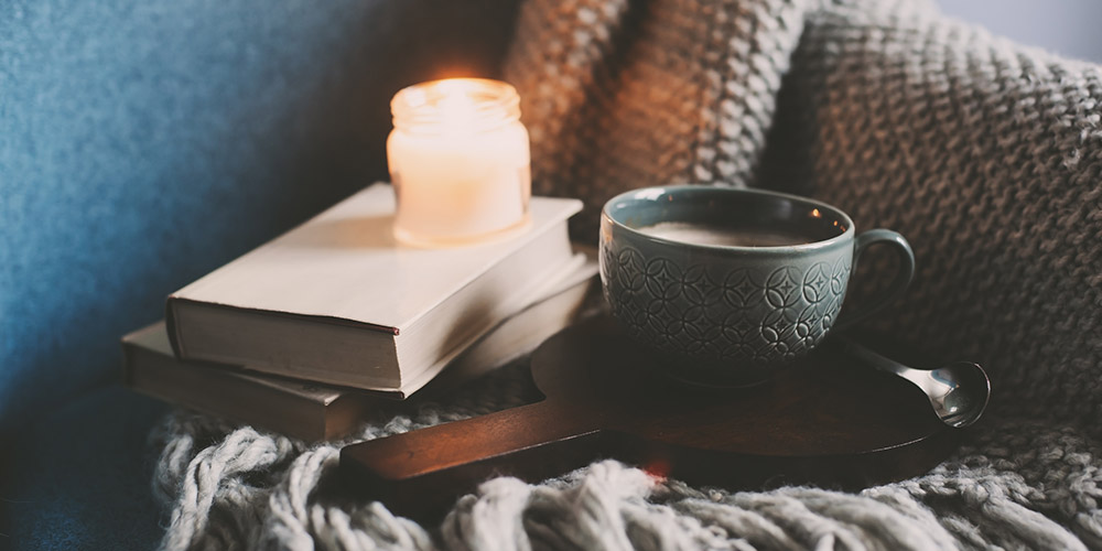 Burning candle rests on two books next to a hot cup of tea on top of a cozy blanket