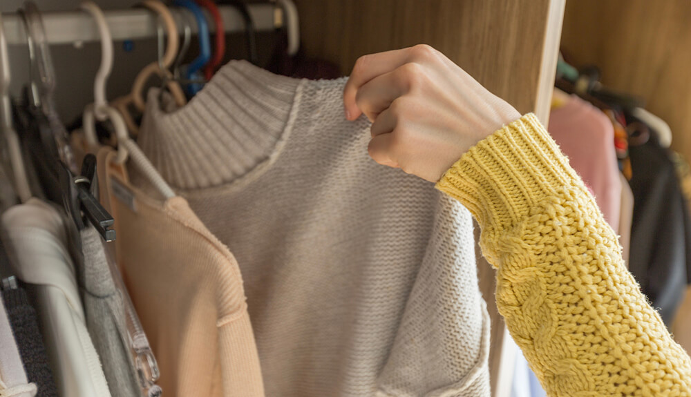 Person lifting sweater on hanger out of closet